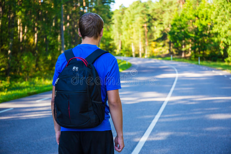 Hiking concept - man with backpack walking on forest road. Hiking concept - young man with backpack walking on forest road royalty free stock photography