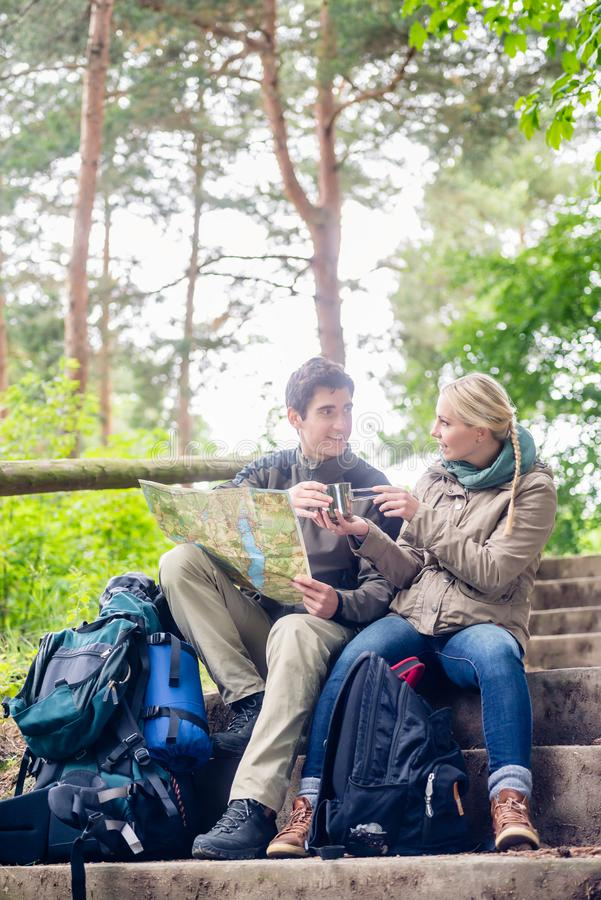 Hiking couple having break on forest trail. Hiking couple, women and man, having break on a forest trail and reading the map royalty free stock photography