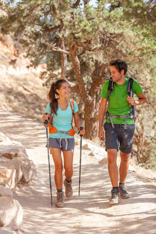 Hiking couple of hikers on trail walk trek with hike poles walking in Grand Canyon. Young Asian girl, Caucasian man, multiracial stock photography