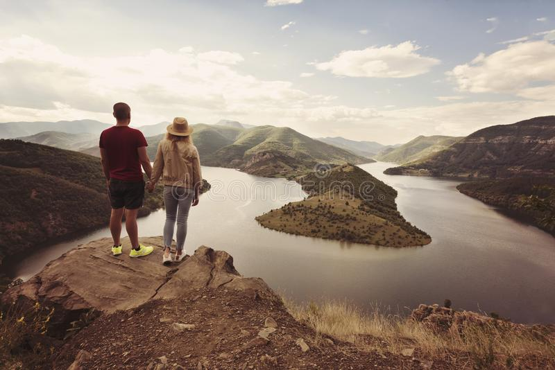 Hiking couple looking at the view holding hands. Location: the meanders of Arda river, Bulgaria stock photography