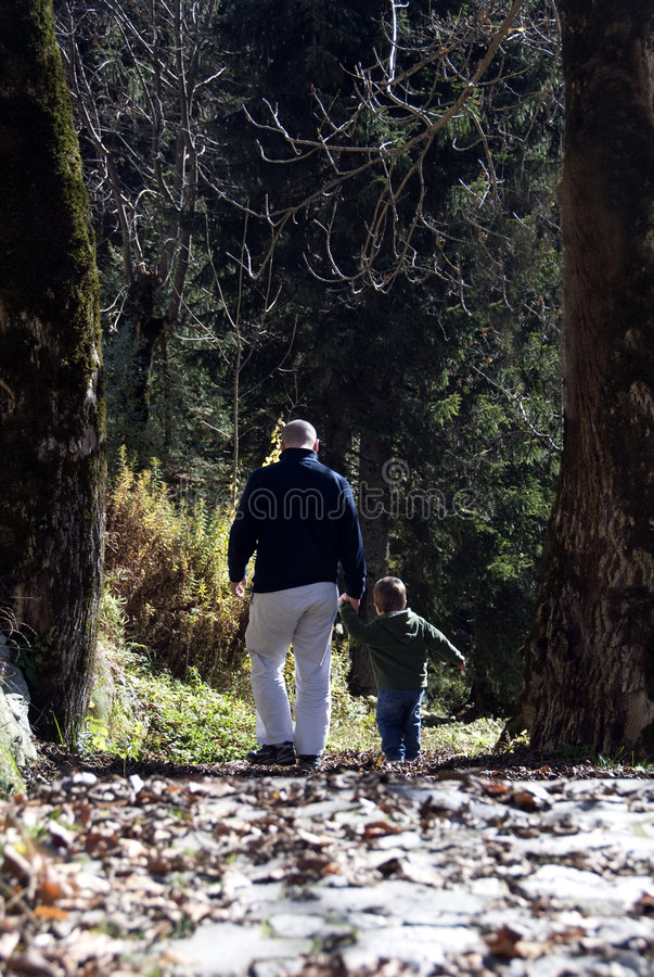 Hiking with dad. Father and son take a hike on a mountain trail together