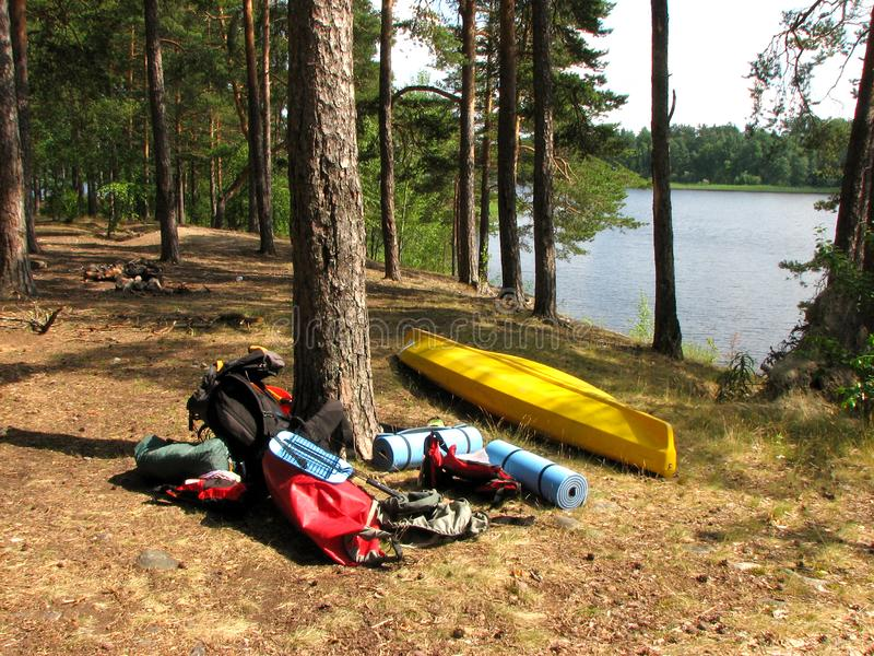 Hiking equipment lies in the sun in the forest by the lake. Kayak, tent, backpack, life jackets, sports mats, barbecue grill. stock photography