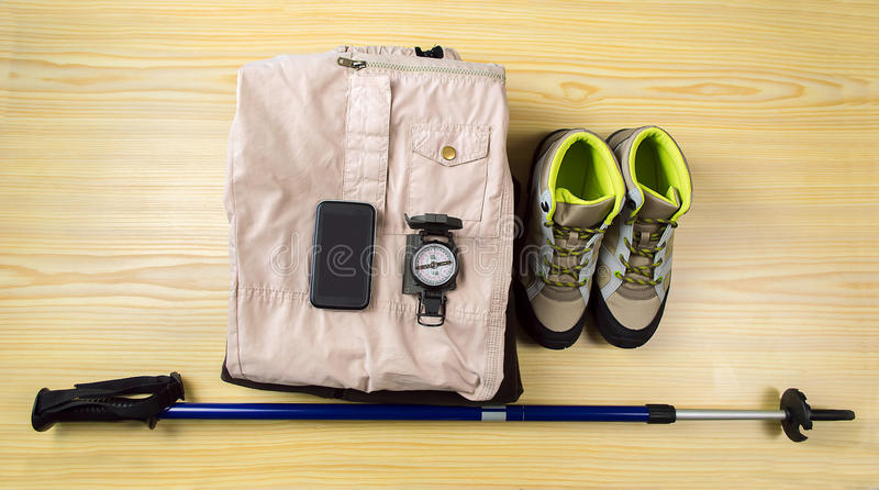 Hiking equipment. Shot of various tools and equipment and telephone for a hiker laid out on a table stock photography