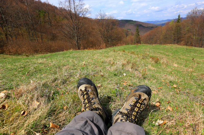 Hiking Feet on meadow. In mountains royalty free stock photography