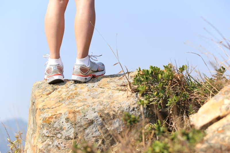 Hiking feet stand seaside rock. Hiking feet stand seaside mountain rock stock images