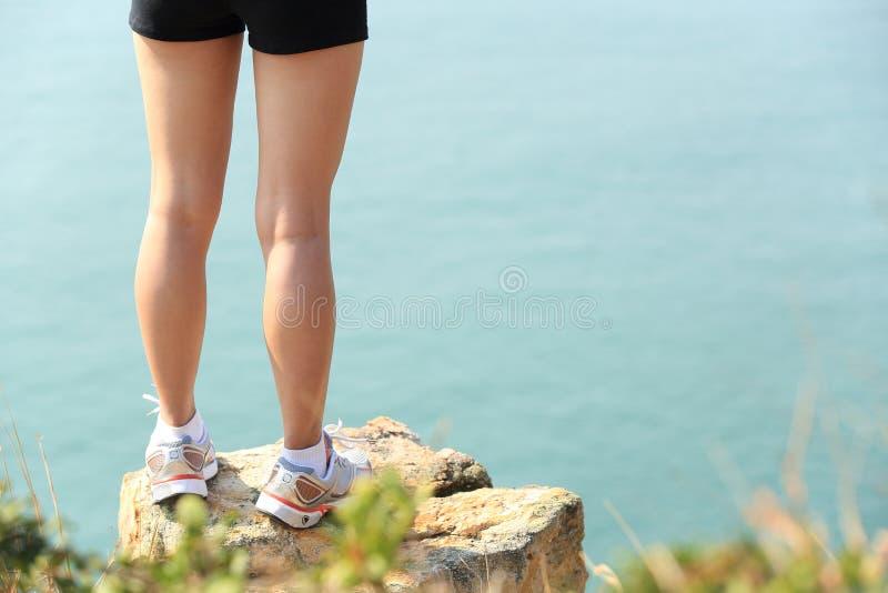 Hiking feet stand seaside rock. Hiking feet stand seaside mountain rock royalty free stock images