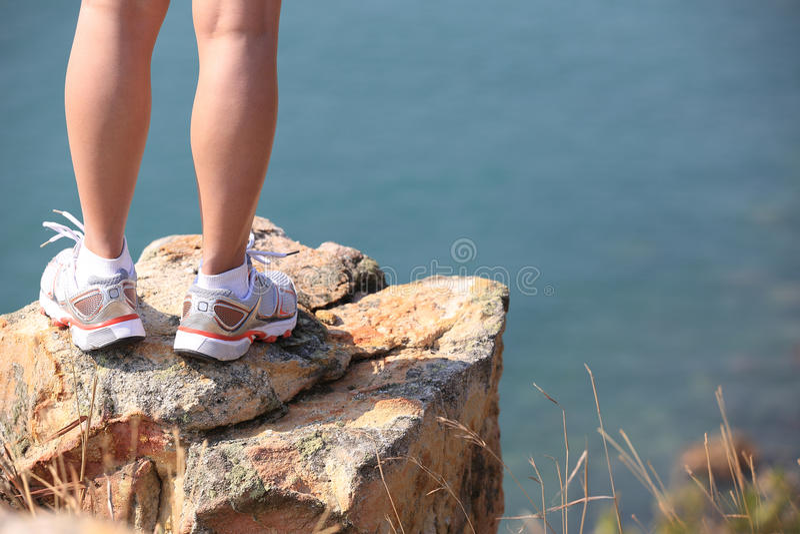 Hiking feet stand seaside rock. Hiking feet stand seaside mountain rock stock image