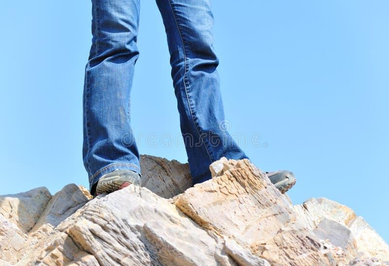 Hiking feet top of mountain. Hiking feet standing on rock royalty free stock photo