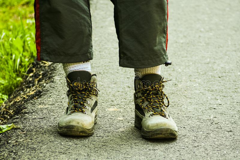 Hiking feet with used hiking boots. A Hiking feet with used hiking boots royalty free stock photo