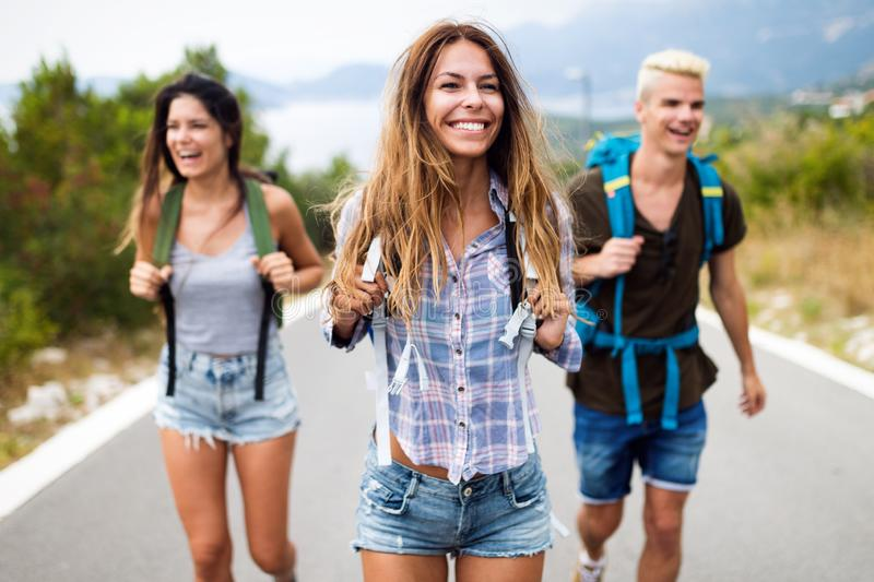 Group of young people with backpacks walking together by the road stock photography