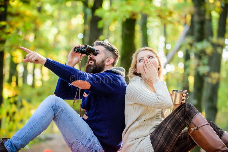 Hiking with friends. surprised girl drink mulled wine. camping and hiking. bearded man shocked watch with binoculars stock image