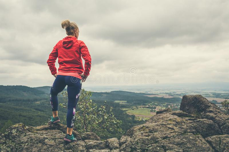 Hiking girl in mountains, looking at view royalty free stock photo