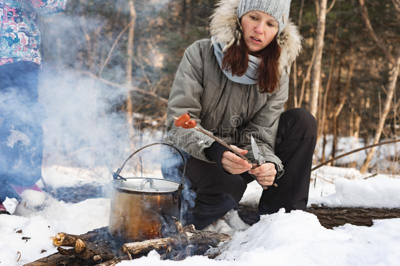 Hiking: Girl prepares food in a pot on a fire in the winter forest. royalty free stock images