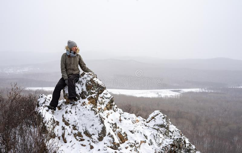Hiking: a girl sits on a snowy top of a cliff. Overcast and light snow. Portrait royalty free stock image