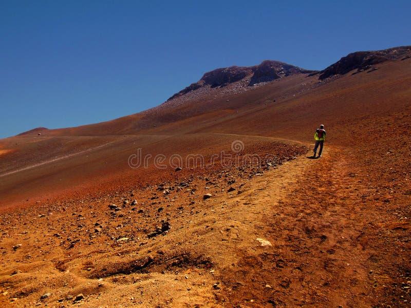 Hiking Haleakala Crater, Maui. A lone hiker in Haleakala National Park follows a trail along the crater to the base of the dormant Hawaiian volcano royalty free stock photo