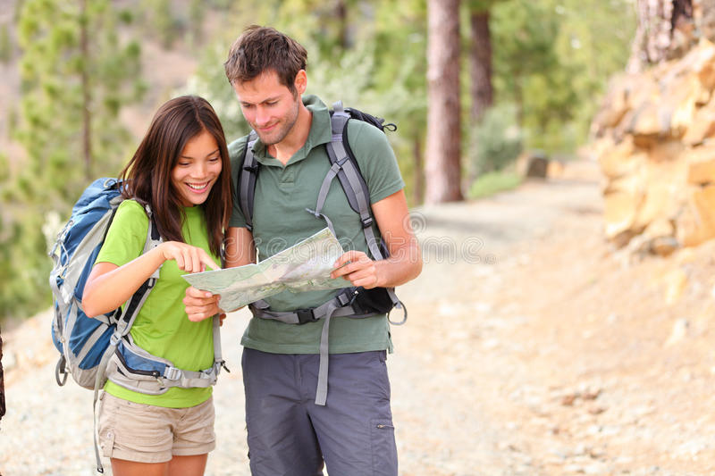 Hiking - hikers looking at map. Couple or friends navigating together smiling happy during camping travel hike outdoors in forest. Young mixed race Asian / royalty free stock photo