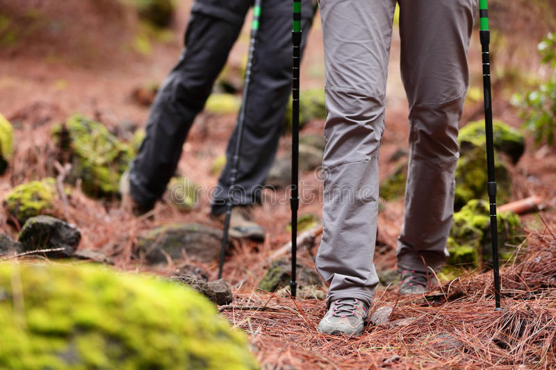 Hiking - Hikers walking in forest with sticks. Hiking - Hikers walking in forest with hiking sticks on path trail in mountains. Close up of hiking shoes and royalty free stock photos