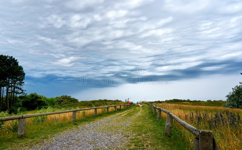 Hiking on isle Hiddensee. Biking walking vacation bike tour weather sky rain storm cloudy background way grass view nature road travel scenery meadow concept stock image