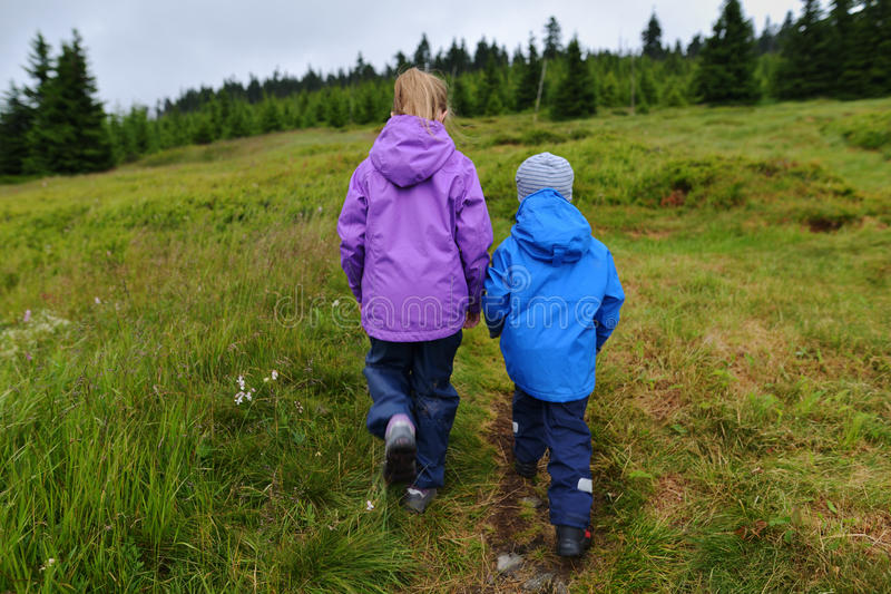 Hiking kids. Siblings in rainy weather clothed in waterproof jackets and trousers. Walking on a beaten boggy track in the mountains royalty free stock photos