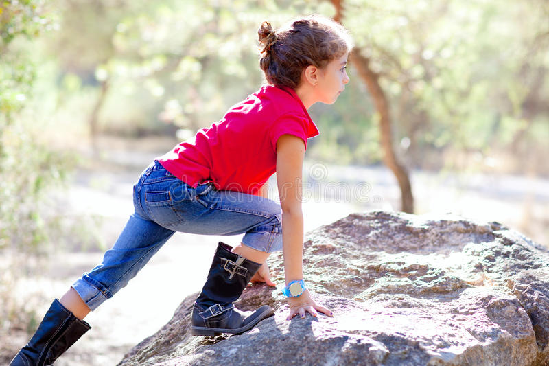 Hiking little girl climbing a rock in forest royalty free stock photos