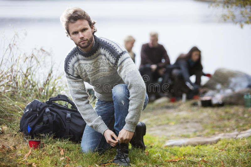 Hiking Male Tying Shoelace With Friends In Background stock photo
