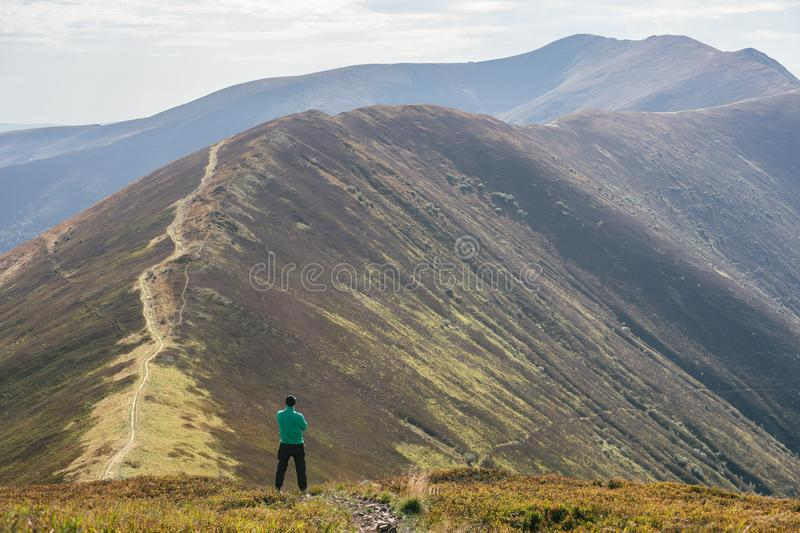 Hiking man, climber or trail runner in mountains, inspirational landscape. Motivated hiker looking at mountain view. Hiking man, climber or trail runner in royalty free stock photography