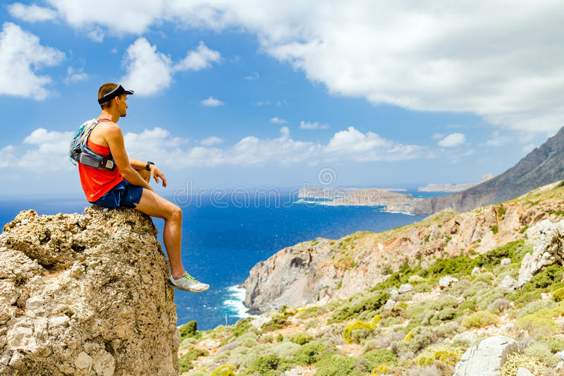 Hiking man looking at inspirational view. Hiker or runner man looking at beautiful ocean and mountains, inspirational landscape view. Fitness and sport royalty free stock photography