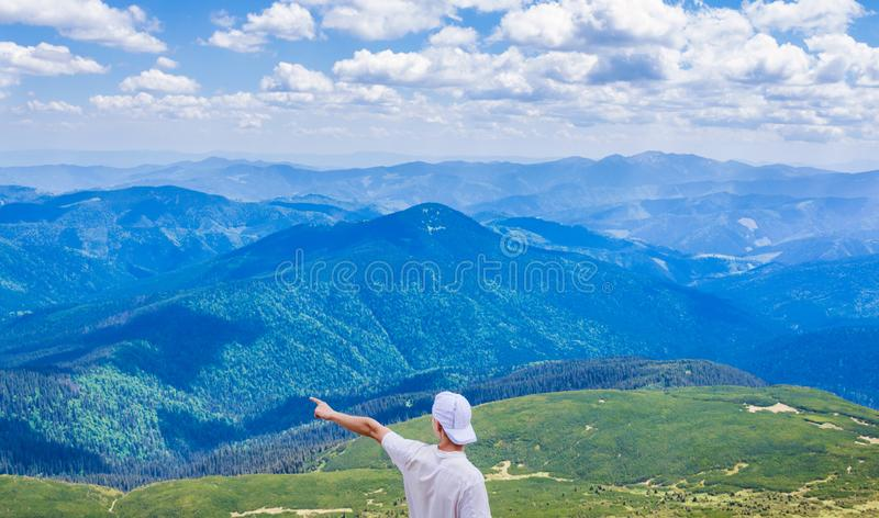 Hiking man pointing on something with his hand. Hipster travelling. Man shows direction with his hand on top of cliff in stock images