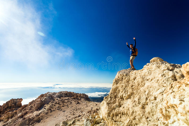 Hiking man or trail runner looking at view in mountains. Man tourist hiker climber or trail runner looking at beautiful inspirational landscape in mountains. Fit stock images