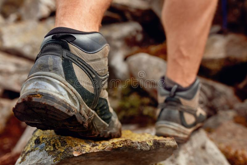 Hiking man with trekking boots on the trail. Closeup of male feet on hiking. Active life concept stock image