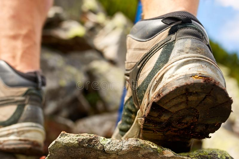 Hiking man with trekking boots on the trail. Closeup of male feet on hiking. Active life concept royalty free stock photo
