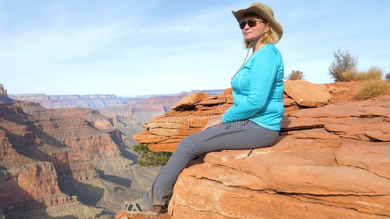 Woman Tourist Sitting On Rock Dangling Her Legs, And Admires Views Grand Canyon stock photo