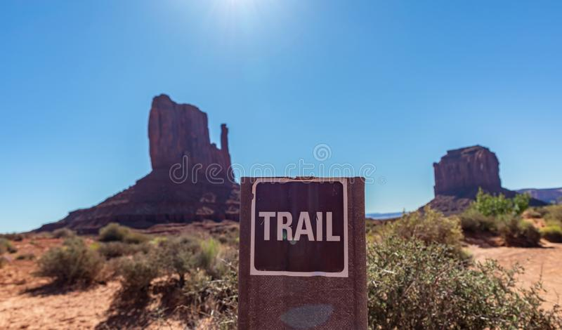 Monument Valley Tribal Park in the Arizona-Utah border, USA. Trail path signage. Hiking in Monument Valley, Trail sign against blur red rocks and blue sky royalty free stock image