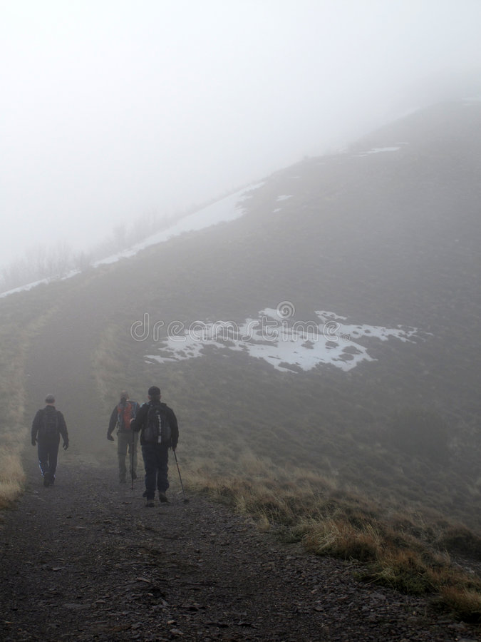 Hiking a Mountain in the Fog. Several people climbing along rocky ridge on a trail in the fog stock photography