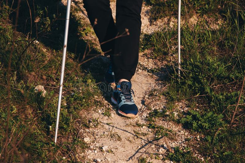 Hiking on the mountain with sticks. Feet on a footpath close-up royalty free stock images