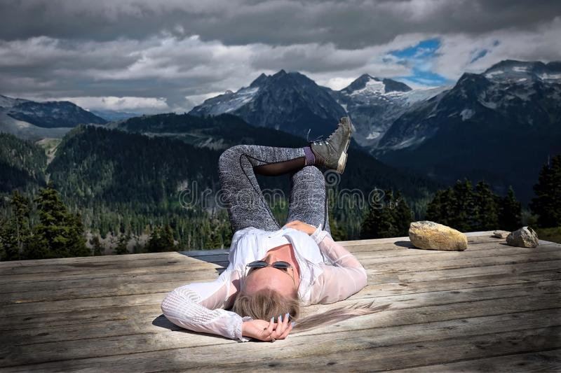 Carefree woman lying down on tent pad after hiking day. stock images