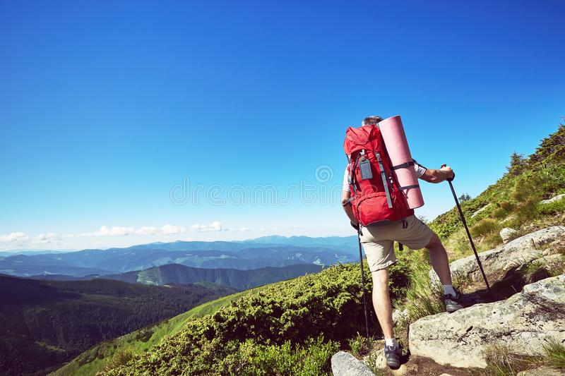 Hiking in the mountains in the summer with a backpack. Hiking in the mountains with a backpack in the summer stock photo