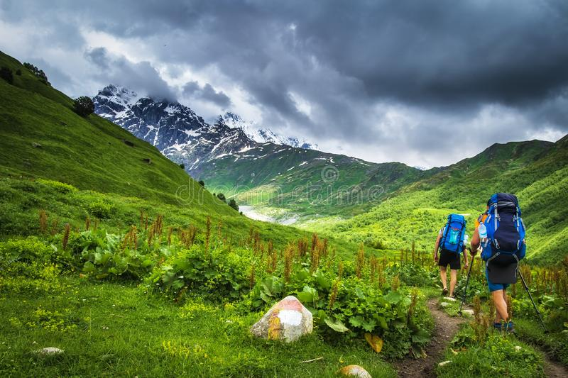 Hiking in the mountains. Tourists with backpacks in mountain. Trekking in Svaneti region, Georgia. Two men hike in mount trail. Sport tourism in georgian royalty free stock images