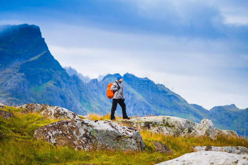 Hiking in Norway. Hiker with red backpack standing on mountains background. royalty free stock photos