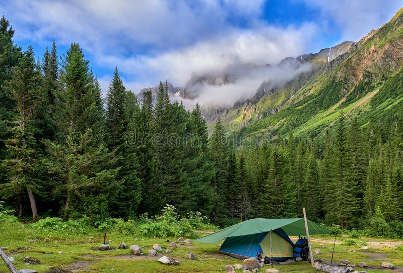 Hiking. One tent is set near mountain forest royalty free stock photo