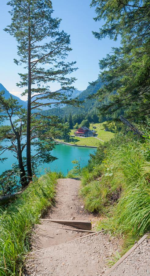 Hiking path along the lakeside of achensee, view to gaisalm hut, vertical format. Hiking path along the lakeside of achensee, view to gaisalm hut, vertical panel stock image