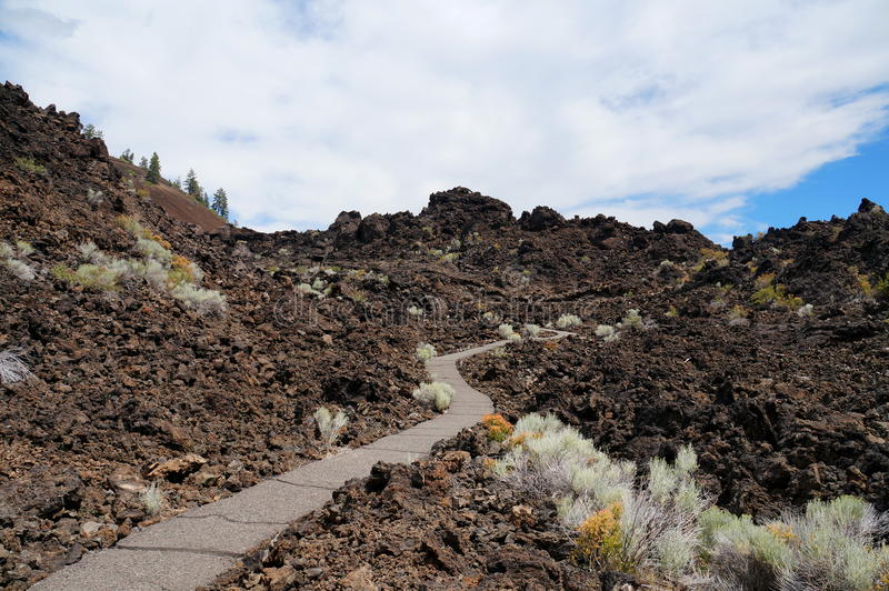 Hiking path in a gigantic lava field of an old volcanic eruption. Reddish black volcanic basalt rock from the eruption of a shield volcano 11.000 years ago. The royalty free stock photography