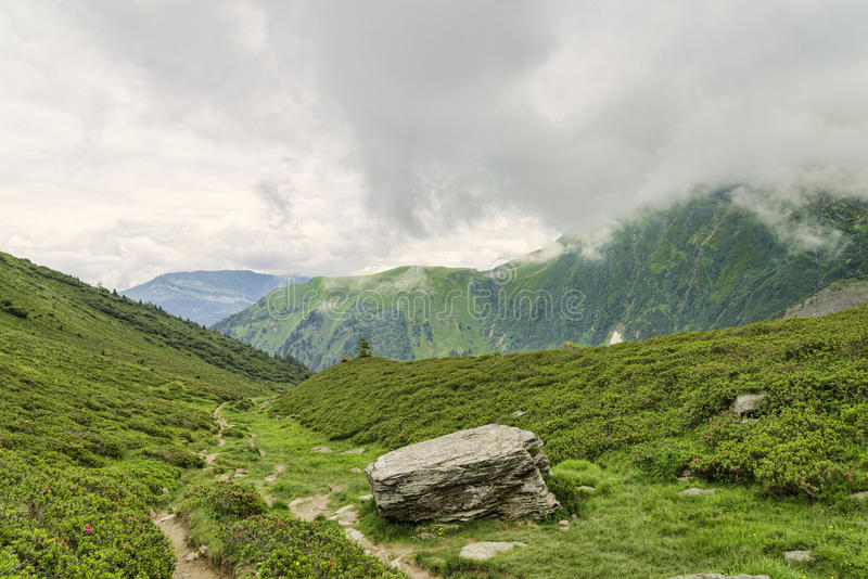 Hiking path among green alpine valley. In France royalty free stock image