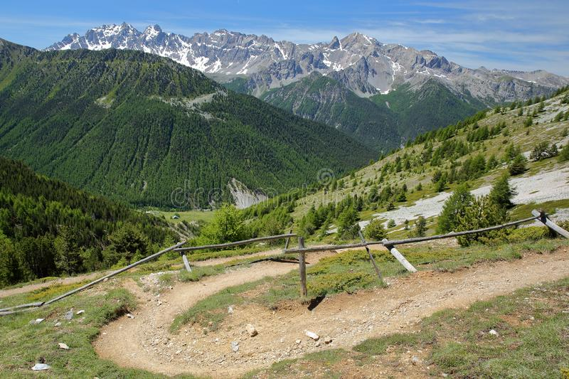 Hiking path  leading to Fromage pass above Ceillac village, Queyras Regional Natural Park, Southern Alps. France, with mountain range covered with snow and royalty free stock image