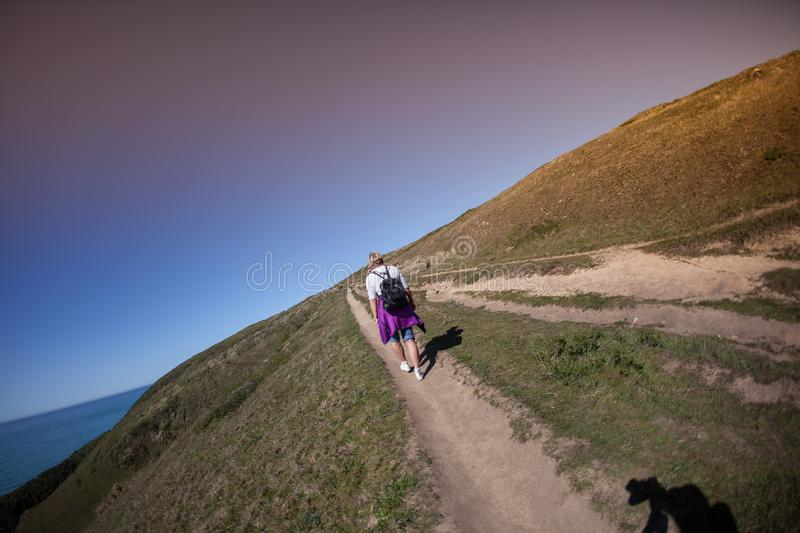 Hiking path trail hiker back pack. Point Reyes, United States - March 03, 2012 : This hilly grass land is hikers dreamland. Paths all around this special place stock photo