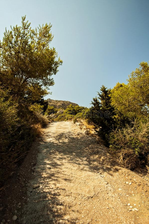 Hiking on a pathway to hill and to forest on a sunny day in Greece. Rhodes royalty free stock images
