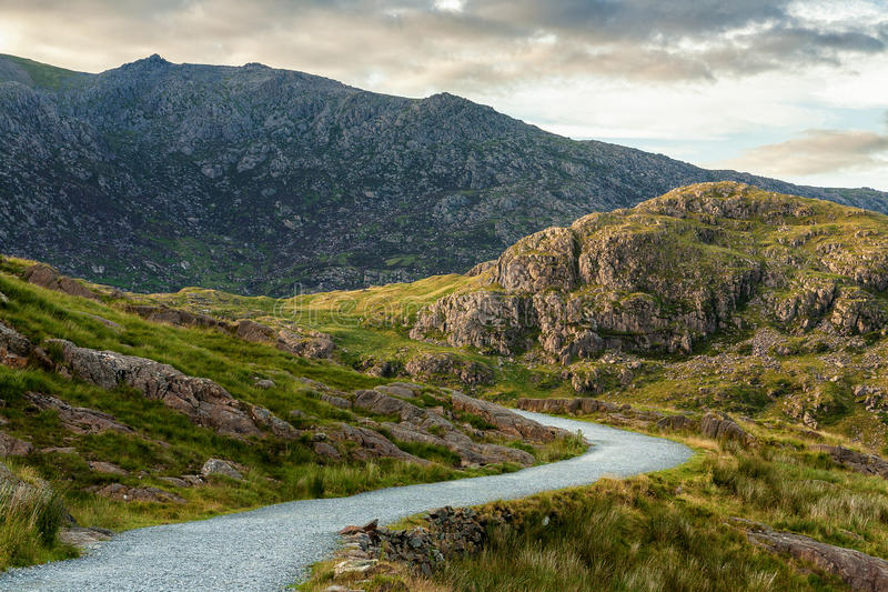 Hiking pathway to Snowdon peak, Wales. Curved hiking pathway called Miner´s track to Snowdon peak in Wales, United Kingdom. Cloudy summer sunset light royalty free stock photos