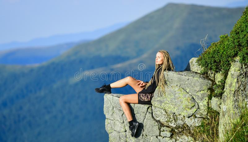 Hiking peaceful moment. Enjoy the view. Tourist hiker girl relaxing edge cliff. Dangerous relax. Extreme concept. On royalty free stock image