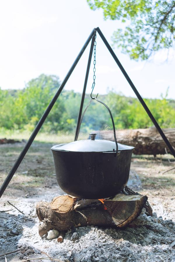 Hiking pot, Bowler in the bonfire. Fish soup boils in cauldron at the stake. Traveling, tourism, picnic cooking royalty free stock photo