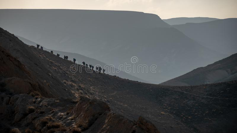 Hiking Ramon Crater. People silhouettes Hiking Ramon Crater, Israel stock photography